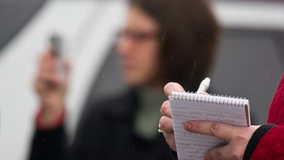 A blurred photo of a journalist and a notepad