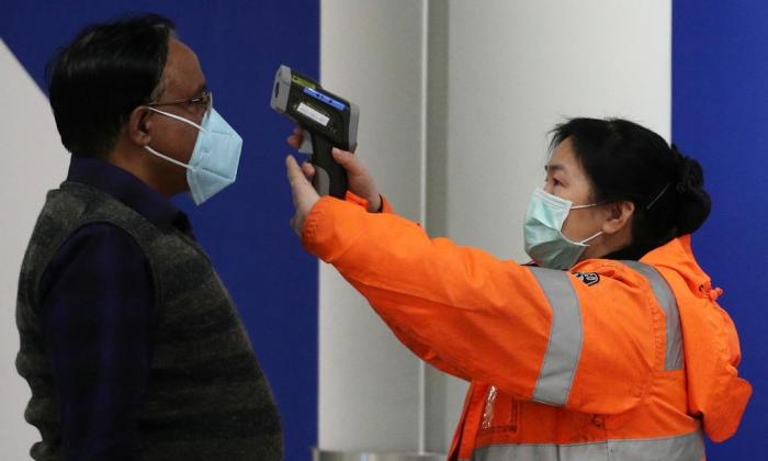 A passenger arriving in Hong Kong gets his temperature checked by a worker using an infrared thermometer on Feb 7, 2020