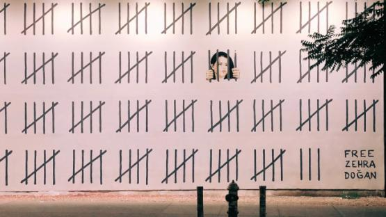 Tally marks painted on a wall, behind one set is a woman painted as though looking through jail bars, in the corner text reads 'Free Zehra Doğan'