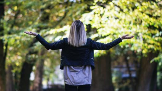 The back of a woman shrugging facing trees in daylight