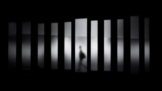 Man walking behind bars