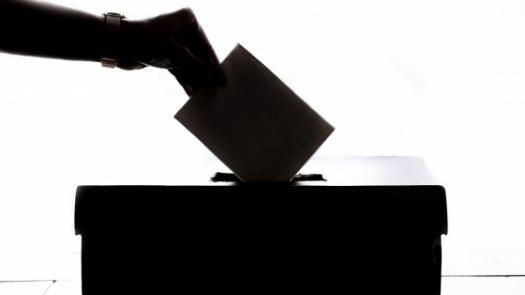 Hand submitting voting ballot into box
