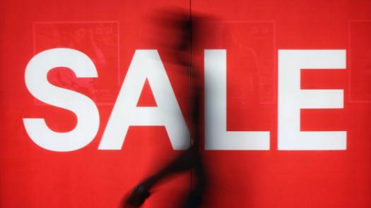"figure of a man in front of a window displaying the word ""SALE"""