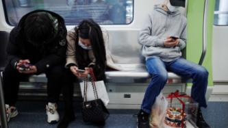 People using phones on public transport
