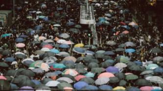 Crowds using umbrellas