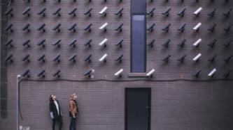 two women looking at surveillance camera art installation